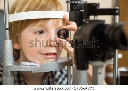 Closeup of male optician's hand checking boy's eye with lens in store - stock photo