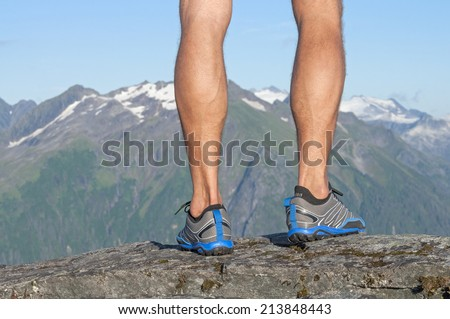 Closeup of male runner's bare legs in running shoes standing on top of rocky summit with magnificent scenic view of snow capped mountains in distance - stock photo