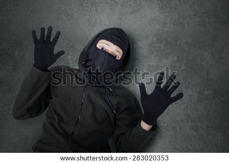 Closeup of male thief with balaclava looking at the camera with fear expression after caught - stock photo
