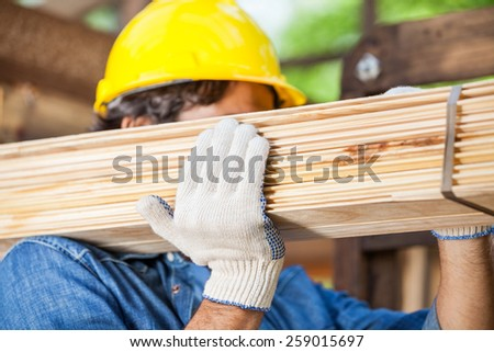 Closeup of male worker carrying tied wooden planks at construction site - stock photo
