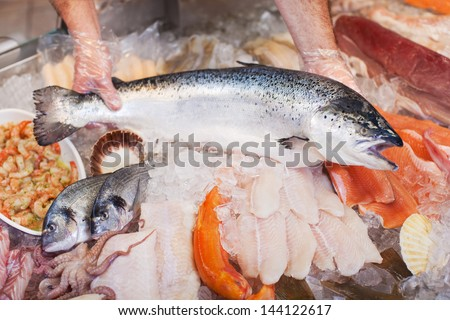 Closeup of male worker's hands keeping fish for preservation - stock photo