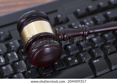 Closeup of mallet on computer keyboard in courtroom - stock photo
