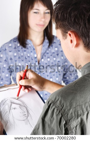 closeup of man drawing portrait of young woman, view from back - stock photo