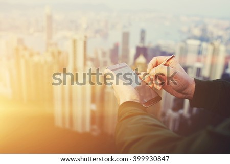 Closeup of man economist is typing something on mobile phone touch screen with copy space by using stylus. Closely of successful businessman is using cell telephone before meeting with client  - stock photo