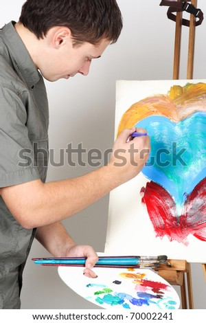 closeup of man holding brushes and palette, painting abstract picture with heart - stock photo