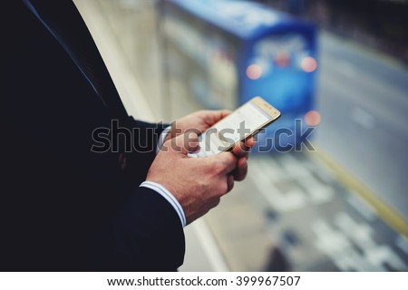 Closeup of man office worker is booking on-line via mobile phone plane ticket for his business trip overseas. Closely of male successful managing director is typing e-mail letter on cell telephone - stock photo
