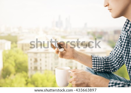 Closeup of man on city background holding coffee cup and using smart phone - stock photo