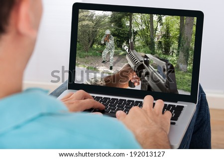 Closeup of man playing action game on laptop at home - stock photo