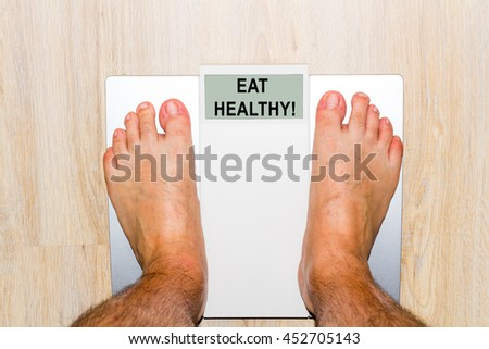 Closeup of man's feet on weight scale - stock photo