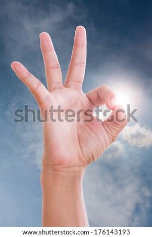 Closeup of man's hand gesturing - showing sign ok (okay) Ok in sky.  - stock photo