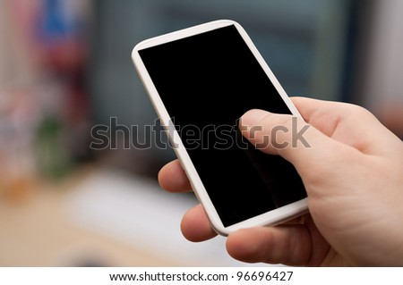 Closeup of Man's Hand Touching Screen of Smartphone in Office - stock photo