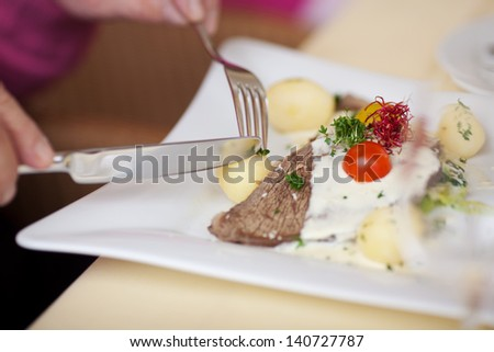 Closeup of man's hands holding fork and knife to cut potato at restaurant table - stock photo