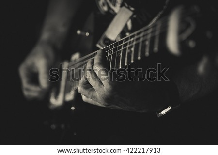 Closeup of man's hands playing guitar on the concert. Guitarist. Monochrome. Music concept - stock photo
