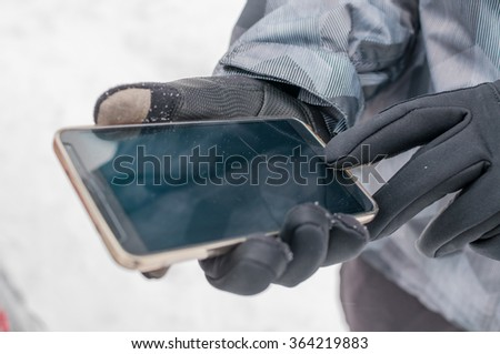 Closeup of man using smartphone in winter with gloves for touch screens - stock photo