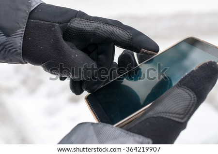 Closeup of man using smartphone in winter with winter gloves for touch screens - stock photo
