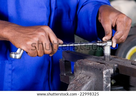 closeup of man with spanner working on machine part - stock photo