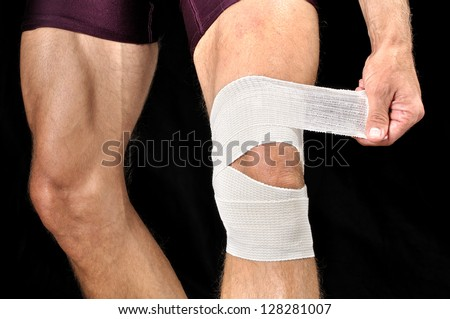 Closeup of man wrapping knee with sports wrap on black background - stock photo