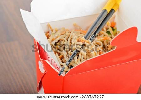 Closeup of meat and noodles in red take away container. Shallow depth of field. - stock photo