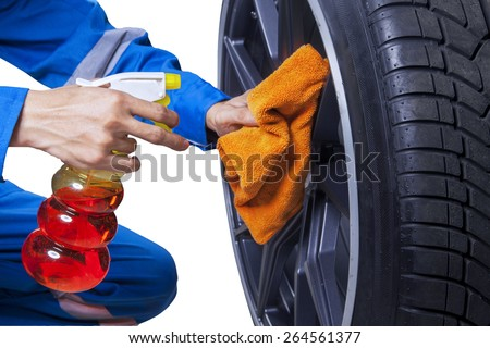 Closeup of mechanic person using a cloth and spray to clean the tire rim - stock photo