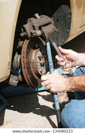 Closeup of mechanic's hands working on front disc brakes of a car. - stock photo