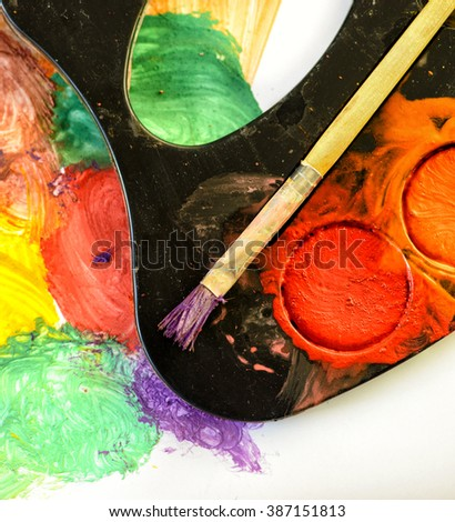 Closeup of messy, used water-color paint-box and paint brush - stock photo