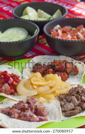 Closeup of Mexican taco meal of four corn tortillas with different kinds of barbecued meat and onion on green plate and bowls of salsa, cucumber, and lime in background on decorative red tablecloth - stock photo