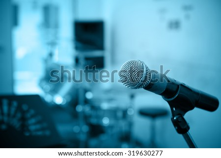 Closeup of microphone in music studio blurred background,blue tone style - stock photo
