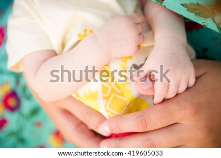 Closeup of mother's hands holding little newborn child. Infant in the hands of his mom.  Mother's love. Woman with baby. - stock photo