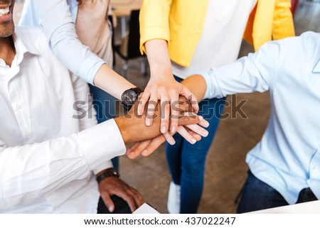 Closeup of multiethnic group of young people standing and joining hands - stock photo