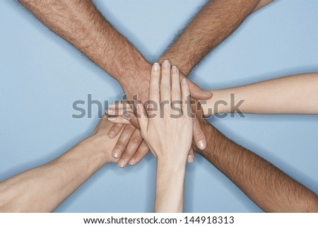 Closeup of multiethnic men and women piling hands on top of each other against blue background - stock photo