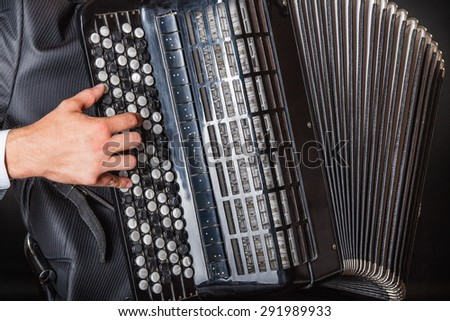 Closeup of musician playing the accordion on a black background - stock photo