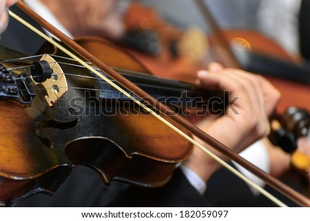 Closeup of  Musician Playing The Violin During a Symphony - stock photo