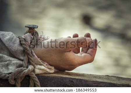 Closeup of nailed hand on wooden cross as a reenactment of the crucifixion of Jesus Christ. - stock photo