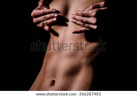 Closeup of naked sexual wet female body of young girl in water drops with beautiful breast nipples and flat belly on black background,  - stock photo
