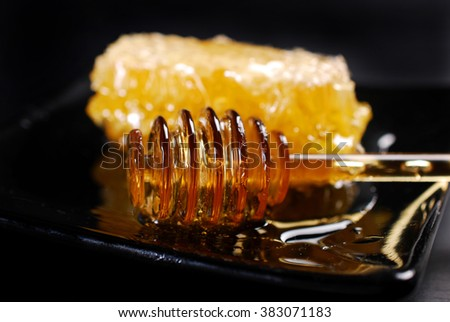 closeup of natural honeycomb and honey spoon on black plate - stock photo