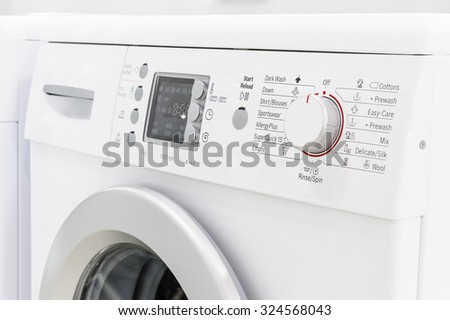 closeup of new white laundry or washing machine, selective focus on control elements - stock photo