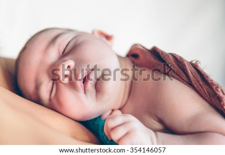 Closeup of newborn baby sleeping peacefully over the mother chest. Maternity and baby care concept. - stock photo