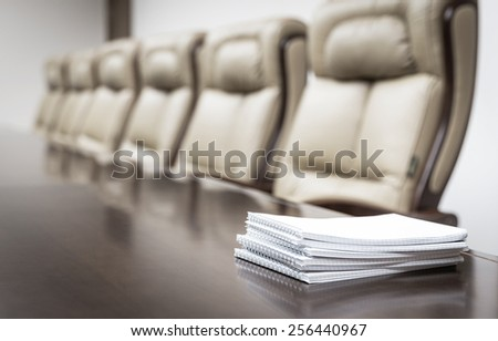 Closeup of notebooks on table in empty corporate conference room before business meeting in office - stock photo