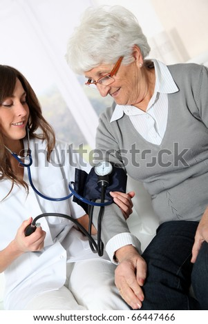 Closeup of nurse checking senior woman blood pressure - stock photo