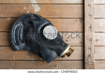 Closeup of old gas mask on wooden box - stock photo