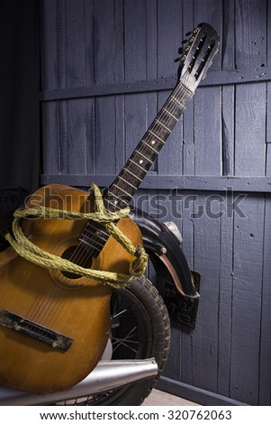 Closeup of one acoustic string light brown color wooden musical instrument of guitar with beautiful shape in rope indoor in studio standing near chrome bike on grey wooden backdrop, vertical picture - stock photo
