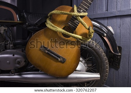 Closeup of one acoustic string light brown color wooden musical instrument of guitar with beautiful shape in rope indoor in studio standing near chrome bike on grey wooden backdrop, horizontal picture - stock photo
