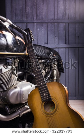 Closeup of one acoustic string light brown color wooden musical instrument of guitar with beautiful shape indoor in studio standing near chrome bike on gery wooden backdrop, vertical picture - stock photo