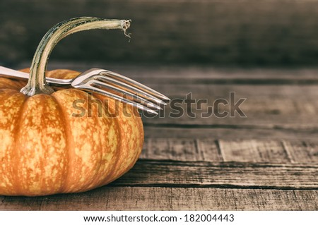 Closeup of one Mini Pumpkin with fork still life on rustic, old used board background with room or space for copy, text, words.  Horizontal.  Old fashioned grunge treatment with a little grain. - stock photo