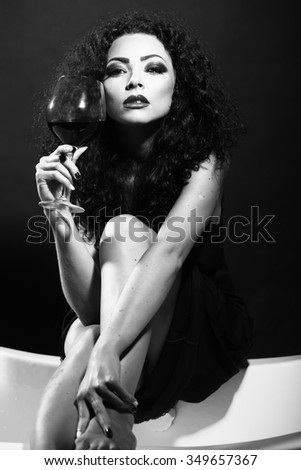 Closeup of one pretty sensual mysterious young brunette sexy woman with long curly hair and bright makeup in dress sitting in studio drinking wine from glass black and white, vertical picture - stock photo