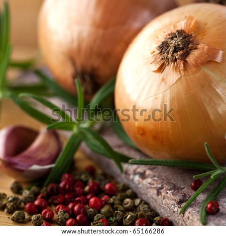 Closeup of onions, herbs and peppercorns - stock photo