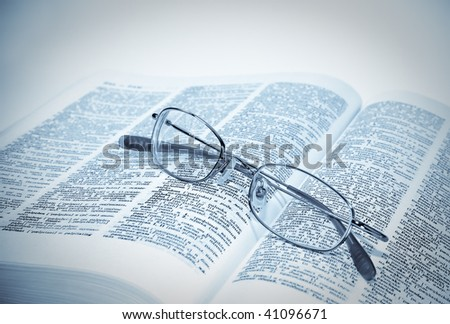 closeup of opened book and glasses. blue tone - stock photo