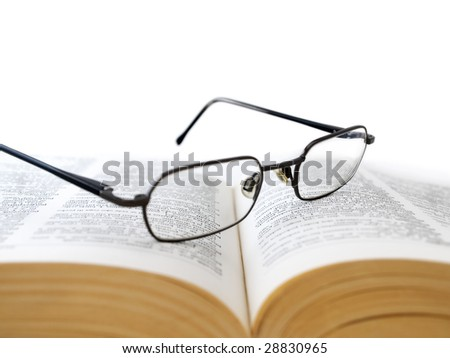 Closeup of opened book with glasses on it, on white background,shallow DOF,focus on glasses - stock photo