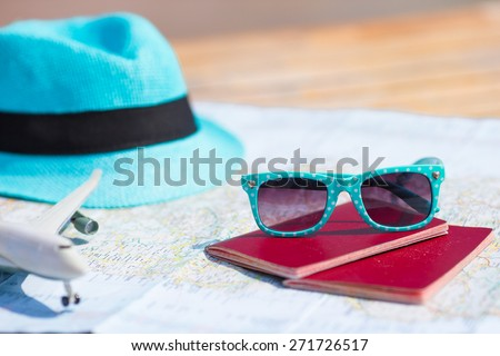 Closeup of passports, toy airplane, sunglasses on the map - stock photo
