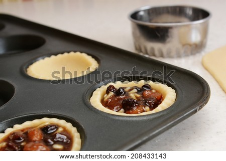 Closeup of pastry case filled with traditional mincemeat, with cutter beyond - stock photo